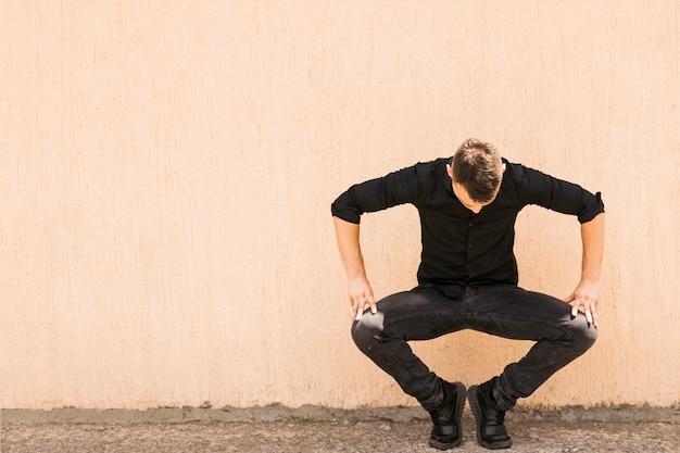 Een jonge man die tegen de muur