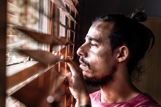 Een jonge man die zichzelf thuis isoleert om tijdens de uitbraak van het coronavirus veilig te blijven, kijkt door de jaloezieën