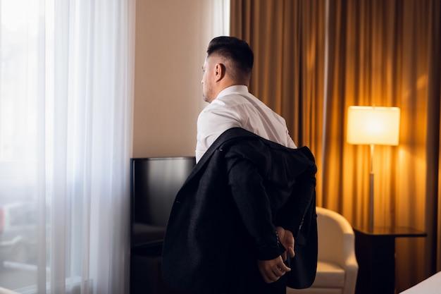 Een jonge man die zijn jas in een hotelkamer opstijgt