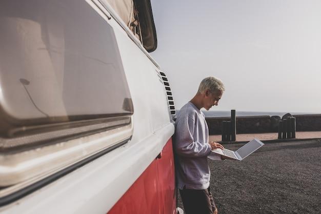 Een jonge man die zijn laptop of computer gebruikt, glimlacht en ernaar kijkt - technologienomadenlevensstijl die reist en de wereld ontdekt met zijn rode minibusje en zijn apparaat om te werken