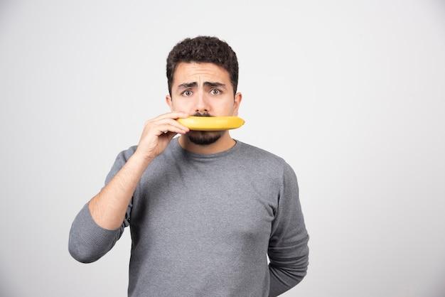 Een jonge man die zijn mond bedekt met een banaan.