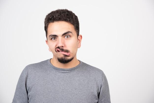 Een jonge man doet een grappig gezicht over een witte muur.