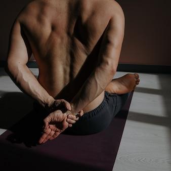 Een jonge man doet yoga in een fitness-studio.