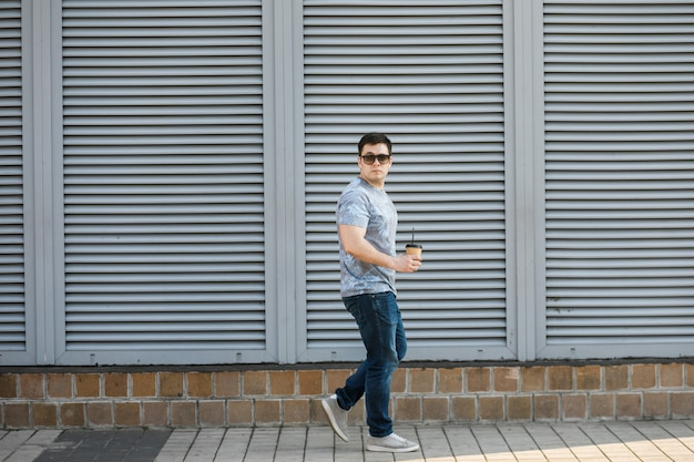 Een jonge man drinkt koffie in de stad en loopt naar buiten.