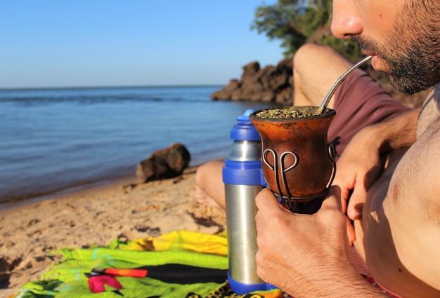 Een jonge man drinkt maat op het strand van de rivier paraná