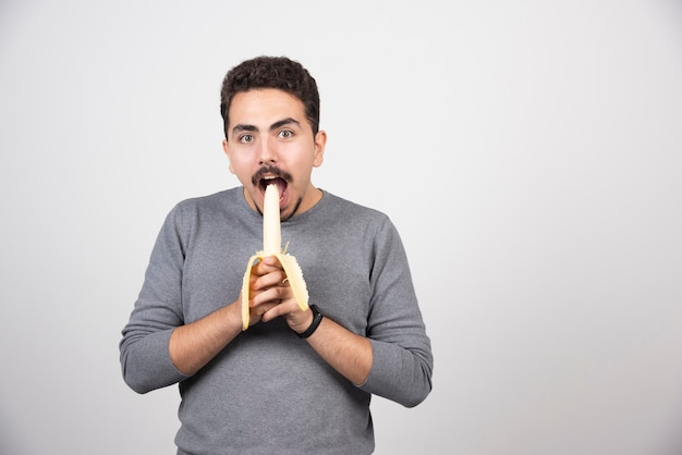 Een jonge man eet een banaan boven een witte muur.