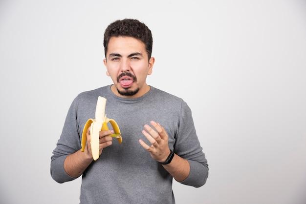Een jonge man eet een banaan met walging.