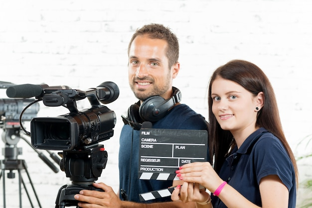 Een jonge man en een jonge vrouw met een filmcamera