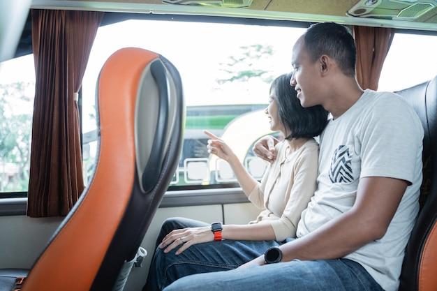 Een jonge man en een jonge vrouw wijzen met de vinger naar het raam terwijl ze onderweg in de bus zitten