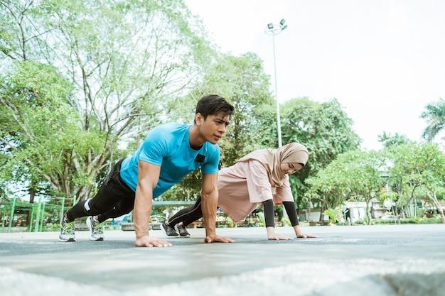 Een jonge man en een meisje in een hoofddoek doen beweging om de borstspieren samen te trainen wanneer ze buiten in het park sporten