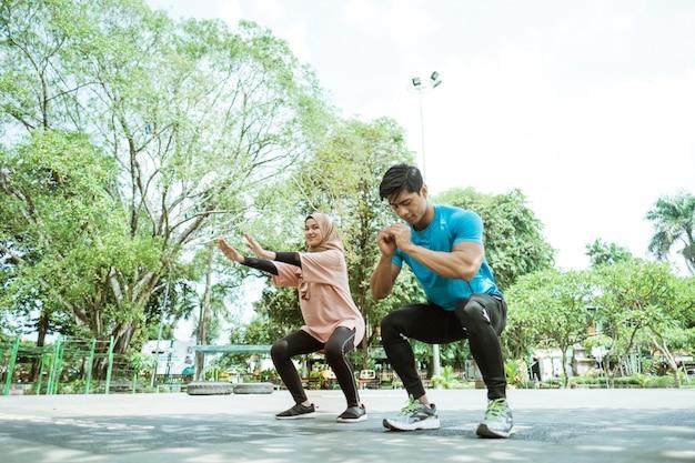 Een jonge man en een meisje in een hoofddoek doen samen hurkbewegingen als ze buiten in het park sporten