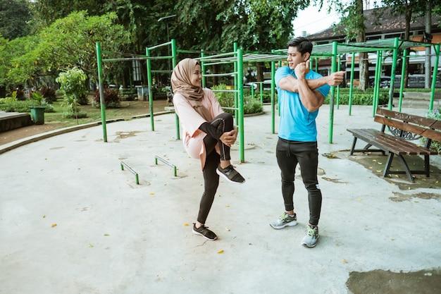 Een jonge man en een meisje in een sluier chatten terwijl ze warming-up bewegingen doen voordat ze in het park gaan trainen