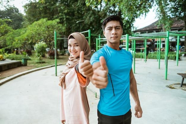 Een jonge man en een meisje in een sluier glimlachen terwijl ze rug aan rug staan met hun duimen omhoog tijdens het sporten in het park