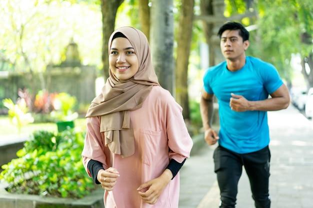 Een jonge man en een meisje in een sluier joggen samen tijdens het sporten in de buitenlucht in het park