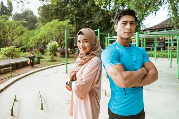 Een jonge man en een meisje in een sluier staan rug aan rug met gekruiste handen tijdens het sporten in het park