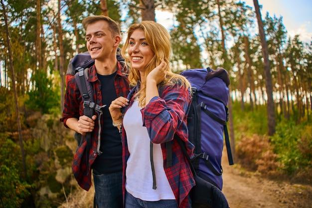 Een jonge man en een vrouw met rugzakken gaan wandelen in de bergen