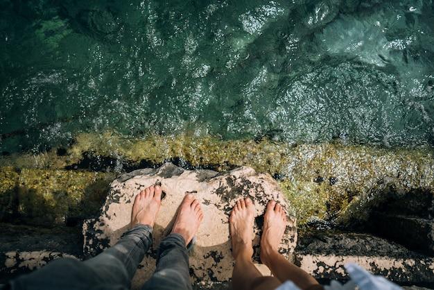 Een jonge man en vrouw hun benen samen over een pier