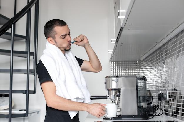 Een jonge man gaat 's morgens werken. poetst tanden in de buurt van een koffiezetapparaat tijdens het wachten op een kopje koffie