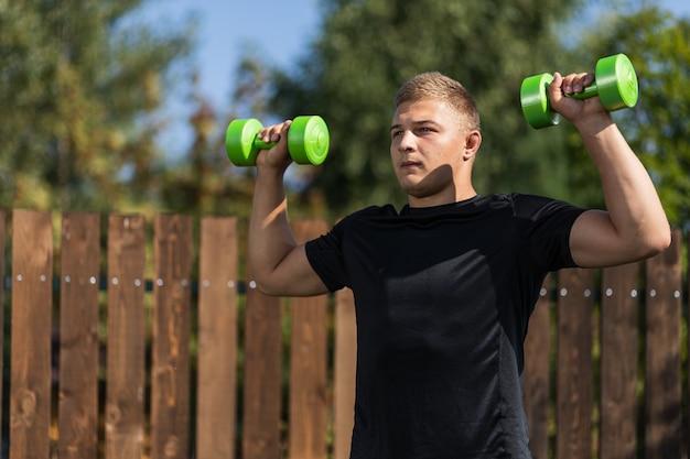 Een jonge man gaat sporten. de atleet doet ochtendoefeningen met dumbells, buigt en trekt zijn hand in de tuin in de zomerdag