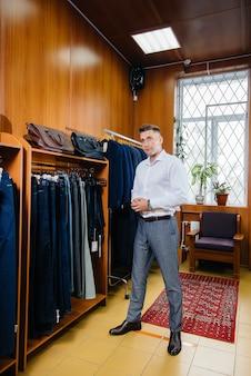 Een jonge man gaat winkelen en pakt een mannenpak.
