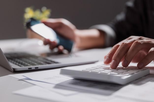 Een jonge man gebruikte een rekenmachine om zijn inkomsten en uitgaven te berekenen