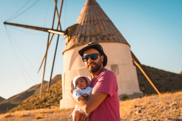 Een jonge man geniet met zijn zoon in het natuurpark cabo de gata, een molen in de stad san jose, almeria