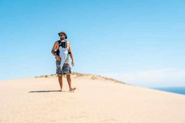 Een jonge man geniet van de zomer met zijn zoon op de zandduin op het strand van monsul in het natuurpark cabo de gata, almeria