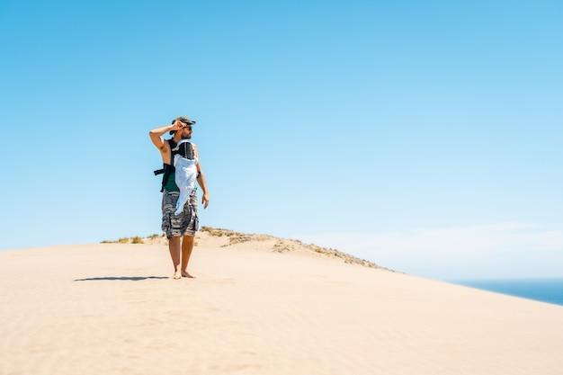 Een jonge man geniet van de zomer met zijn zoon op de zandduin op het strand van monsul in het natuurpark cabo de gata, san jose, almeria