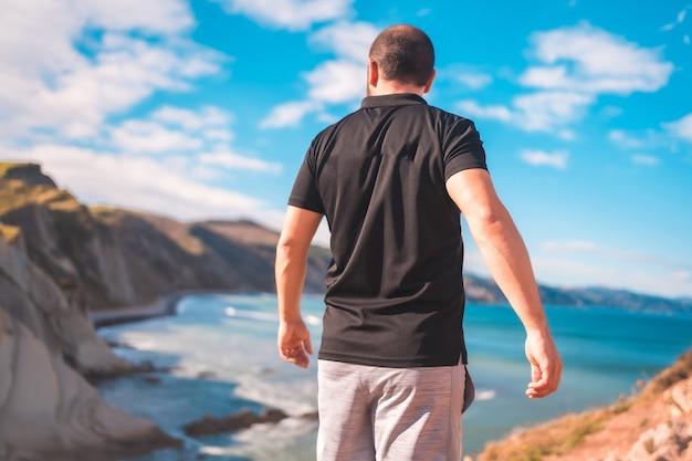 Een jonge man geniet van een zomermiddag aan de kust van het baskenland, zumaia. gipuzkoa