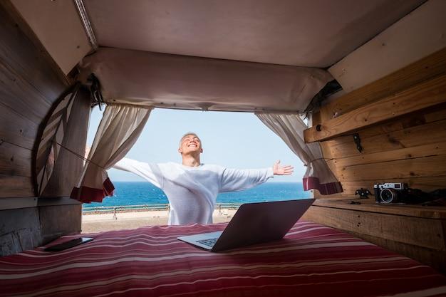 Een jonge man geniet van het buitenleven, reizen en alleen plezier hebben met zijn minibus - nomadische technologie levensstijl - met behulp van en werken met laptop met het strand en de zee op de achtergrond