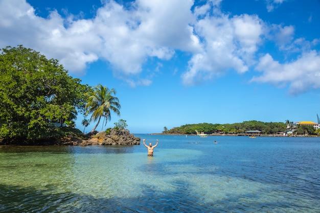 Een jonge man genieten in de caribische zee op west end beach op roatan island. honduras