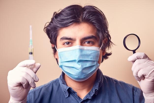Een jonge man glimlacht terwijl hij nitrilhandschoenen met een chirurgisch masker op zijn gezicht draagt