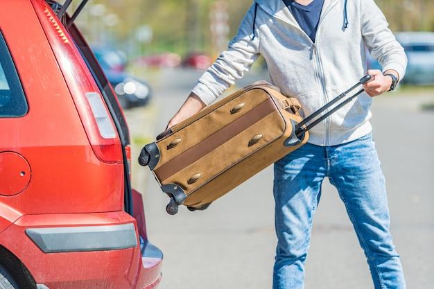 Een jonge man haalt zijn bagage uit de kofferbak van een auto