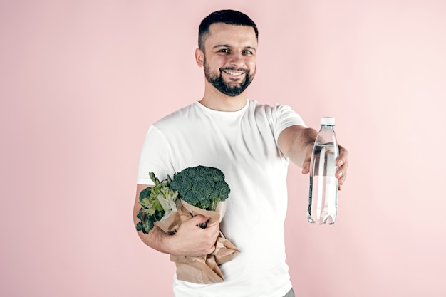 Een jonge man heeft een papieren zak met groenten en een fles water in zijn handen. gezond eten, vegetarisch.