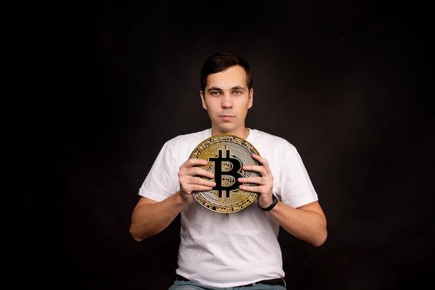 Een jonge man heeft een symbool van de bitcoin-munt, een moderne valuta voor ruilen en aankopen