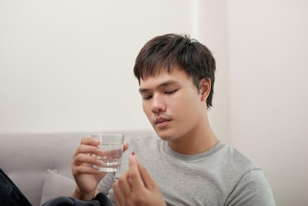 Een jonge man heeft griep, ligt thuis onder een deken, neemt een pil