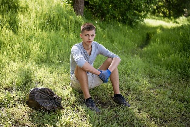Een jonge man heeft het park vrijwillig schoongemaakt van vuilnis en zit op het gras met handschoenen die rusten na het werk