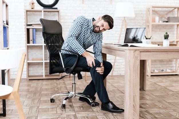 Een jonge man heeft pijn in zijn been hij masseert