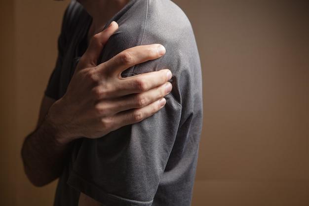 Een jonge man heeft schouderpijn op een bruine achtergrond