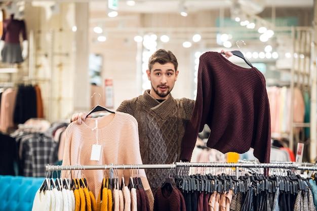 Een jonge man helpt zijn vriendin om de juiste trui te vinden in een kledingwinkel