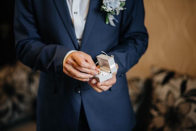 Een jonge man houdt een doos met trouwringen close-up.
