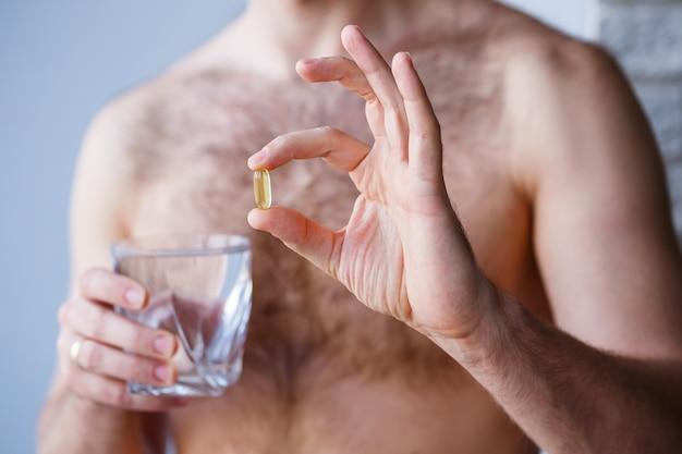 Een jonge man houdt vitamines en een glas water in zijn handen. immuniteit pillen