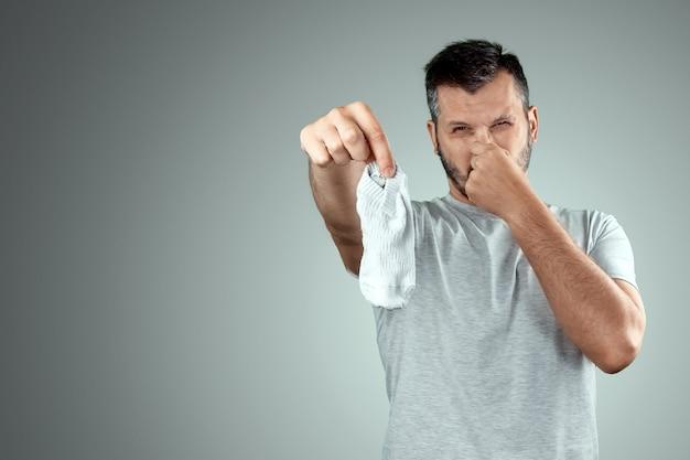 Een jonge man houdt zijn stinkende sokken vast en bedekt zijn neus met zijn hand