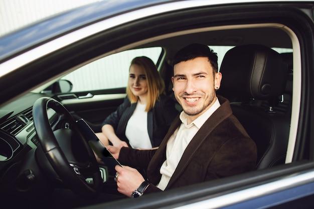 Een jonge man huurt een auto. werknemer van het dealercentrum toont documenten in de auto