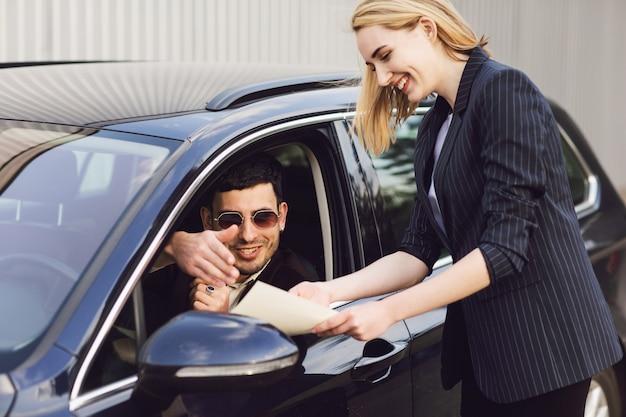 Een jonge man huurt een auto. werknemer van het dealercentrum toont documenten in de buurt van de auto