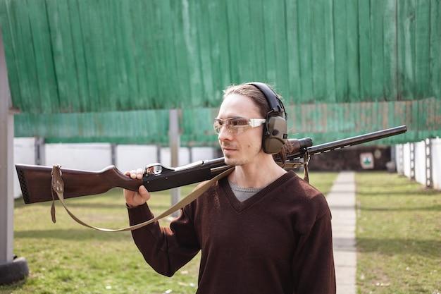 Een jonge man in beschermende bril en koptelefoon. een shotgun met een pumpaction vuurwapen.