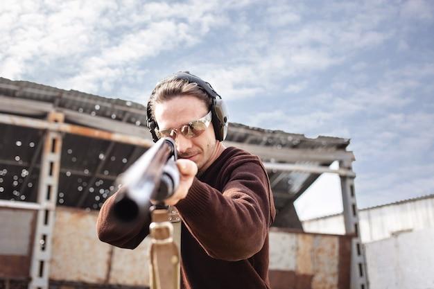 Een jonge man in beschermende bril en koptelefoon. een shotgun met pompactie.