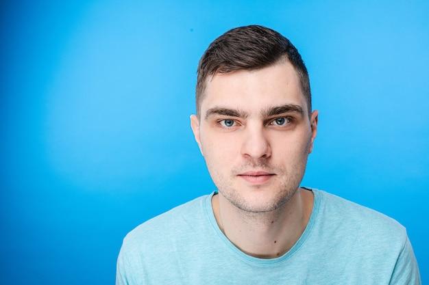 Een jonge man in blauw t-shirt heeft geen emoties, foto geïsoleerd op blauwe achtergrond