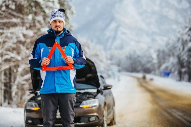 Een jonge man in de bergen houdt het noodsituatiebord achter zich, de kapotte auto