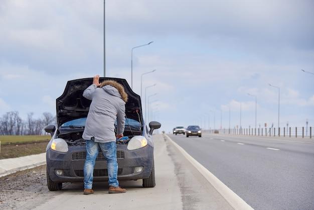 Een jonge man in de buurt van auto met een open kap langs de weg.